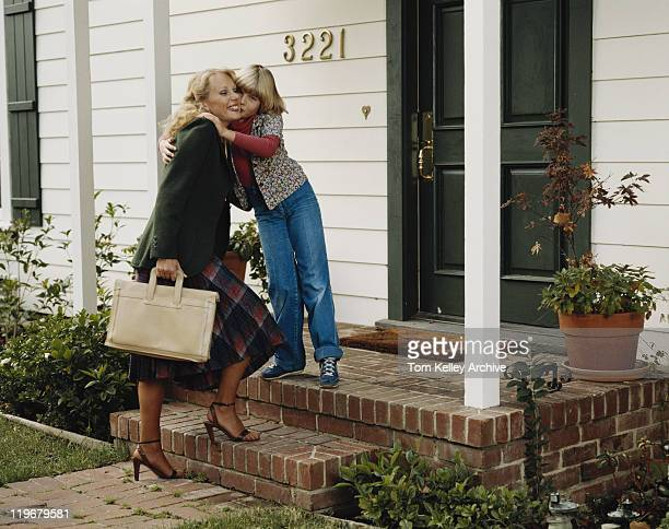 Daughter kissing mother on doorstep