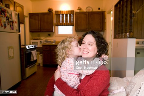 Daughter kissing mother's cheek : Stock Photo