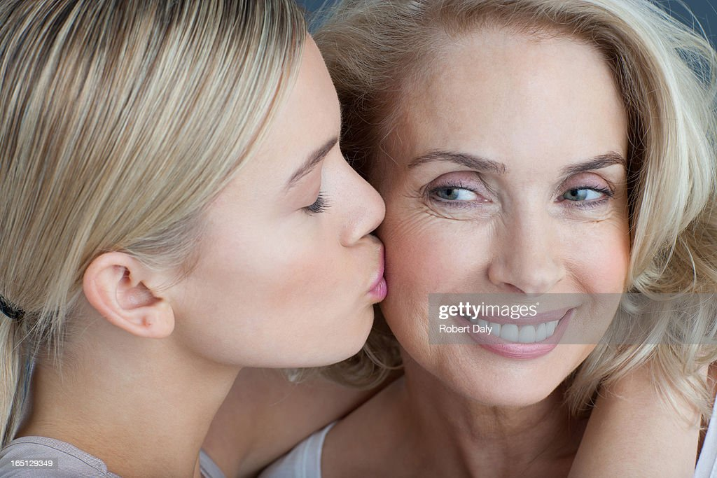 Daughter kissing smiling mother : Stock Photo