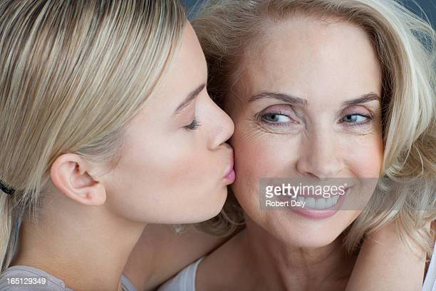 Daughter kissing smiling mother