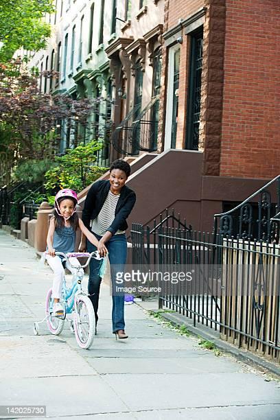 Figlia alle prime pedalate in bicicletta lungo il marciapiede con Madre