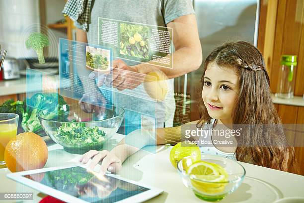 Daughter looking at holograms of recipes on tablet