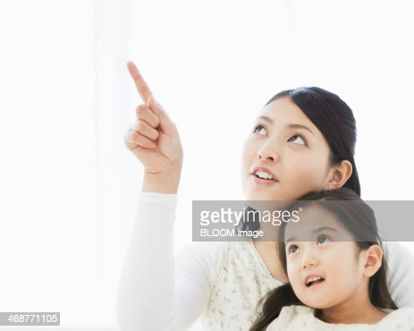 Daughter Looking At Mother Pointing : Stock Photo