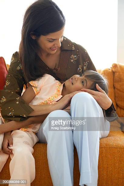 Daughter (8-10) lying on mother, smiling