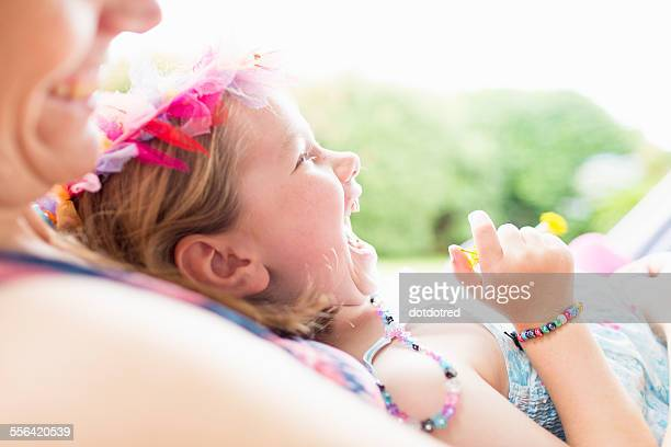 Daughter lying on mothers lap, laughing