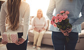 Teenage girl and her mom are hiding flowers and a gift box for their beautiful granny behind backs while grandma is sitting on couch at home