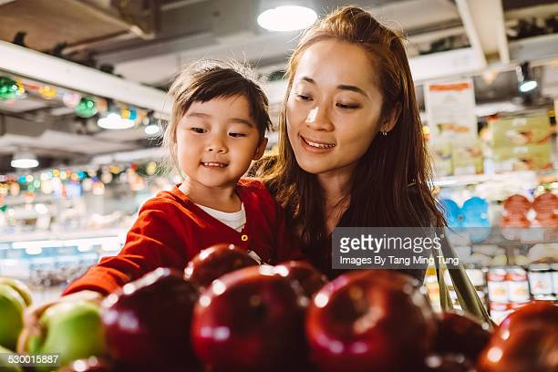 Daughter & mom choosing fruit in supermarket