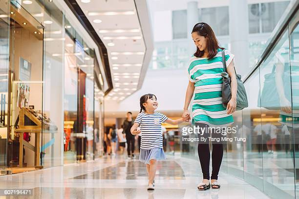 Daughter & mom strolling in shopping mall