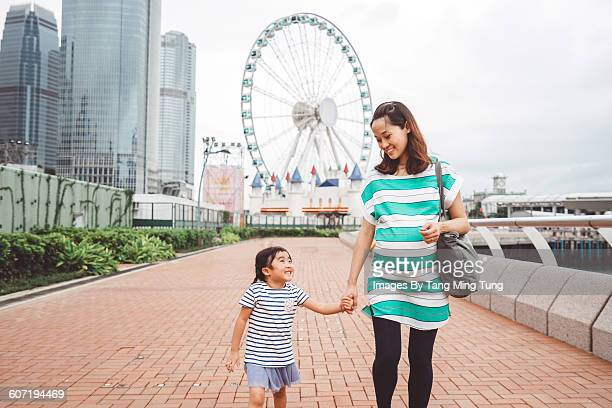 Daughter & mom strolling outside a theme park