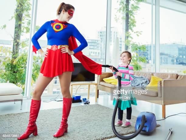 Daughter of superhero vacuuming her cape in living room