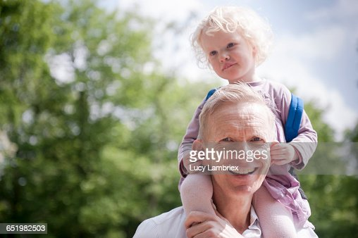 Daughter on father's shoulders, holding his ears : Stockfoto