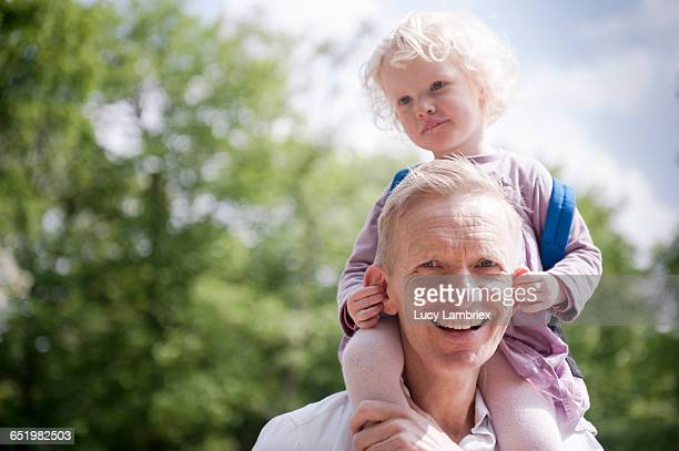 Daughter on father's shoulders, holding his ears