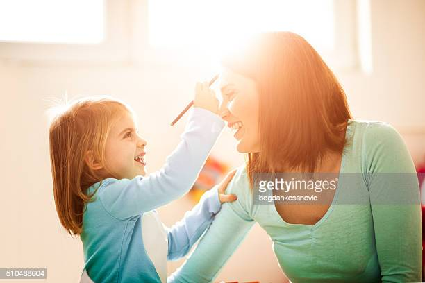 Daughter painting face to her mother