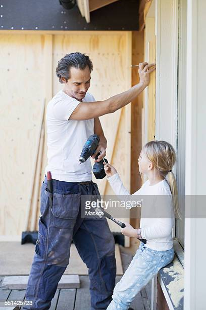 Daughter passing nail to father working on window frame of house being renovated