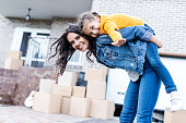 happy daughter piggyback riding mother in front of new house