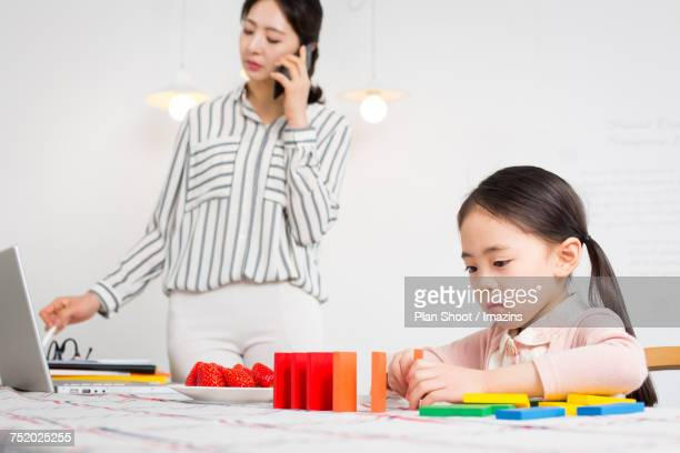 Daughter playing alone with a working mother