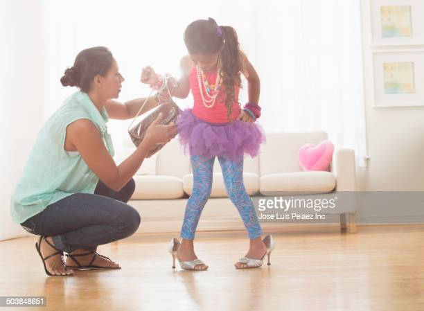 Daughter playing dress up with mother's purse