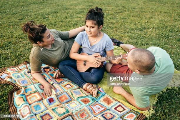 Daughter playing ukulele for parents on picnic