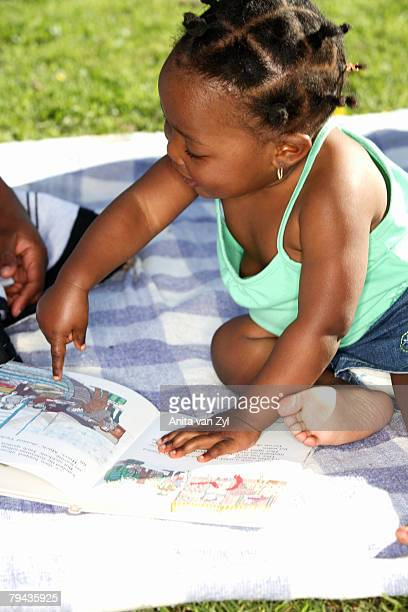 Daughter pointing at pictures in her book. Dewaal Park, Cape Town, Western Cape Province, South Africa