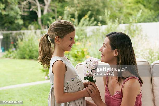 Daughter (7-9) presenting mother with flowers, smiling, side view