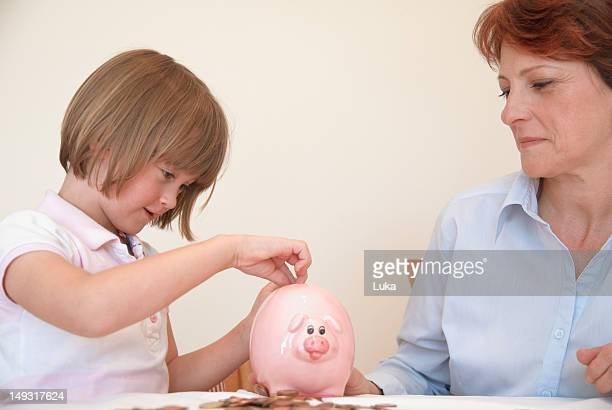 Daughter putting money in piggy bank