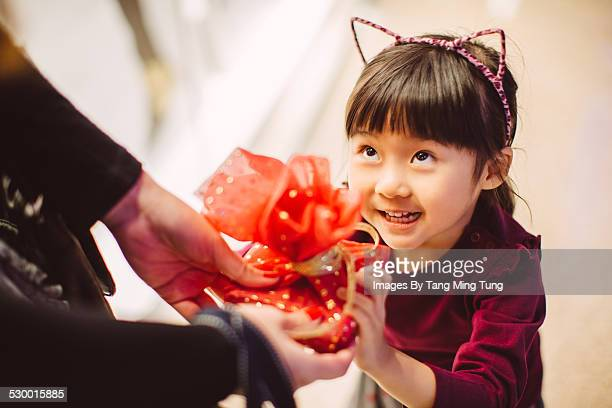 Daughter receiving a gift from her mom joyfully