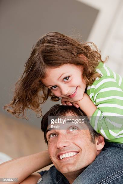 daughter riding on father's shoulders