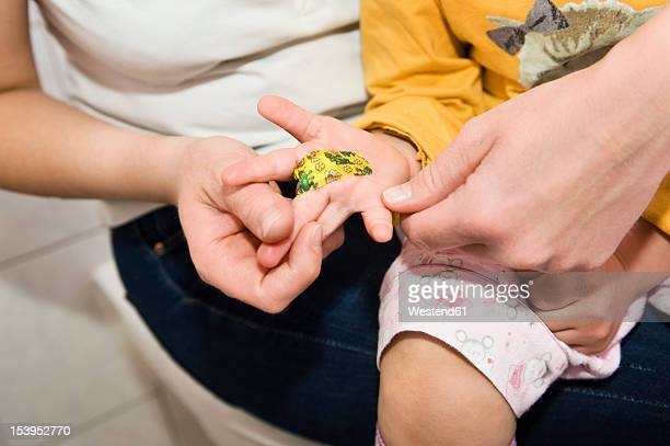 Daughter showing bandage sitting on mother lap in bathroom, close up