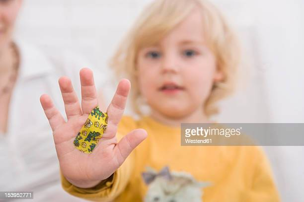 Daughter showing hand with bandage, close up