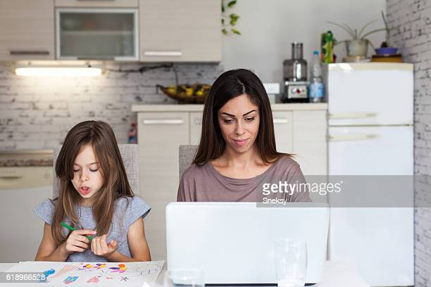 Daughter showing mother at laptop drawing