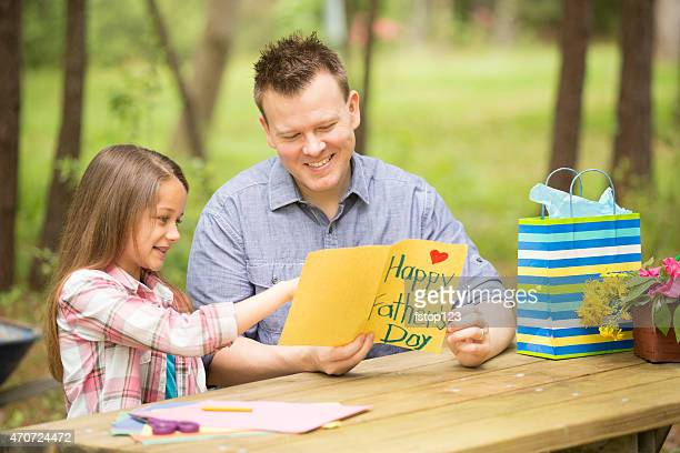 Daughter shows dad handmade Father's Day card. Outdoors. Child, parent.