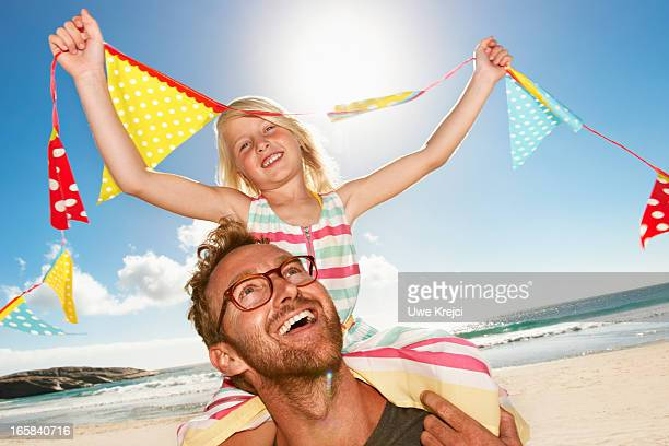 Daughter (6-8) sitting on father's shoulders, smil