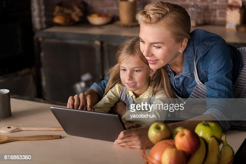 Daughter sitting with her mother in the kitchen : Stock Photo