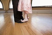Daughter standing on feet of father dancing
