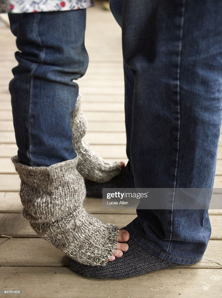 Daughter standing on her father's feet : Stock Photo