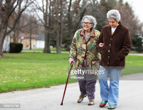 Daughter Supporting Mother Using Cane
