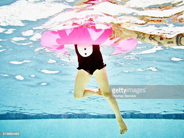 Daughter swimming with pool toy underwater view