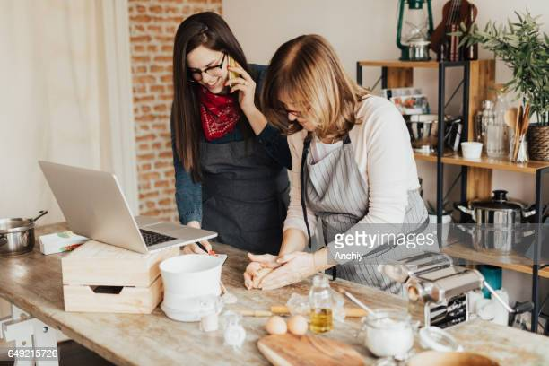 Daughter taking orders from client, Mother kneading dough in domestic kitchen