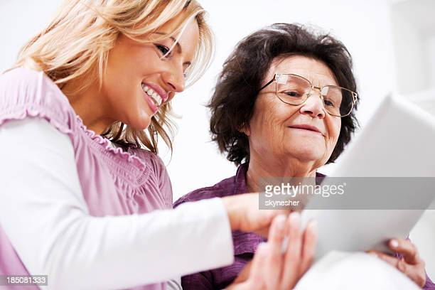 Daughter teaching her senior mother to use touchpad