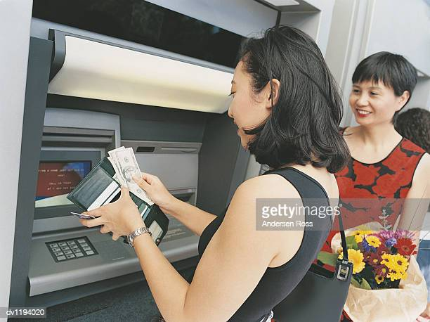 Daughter Using a Cash Machine and Putting Banknotes and Her Bank Card Into Her Wallet Next to Her Mother Holding a Bouquet of Flowers