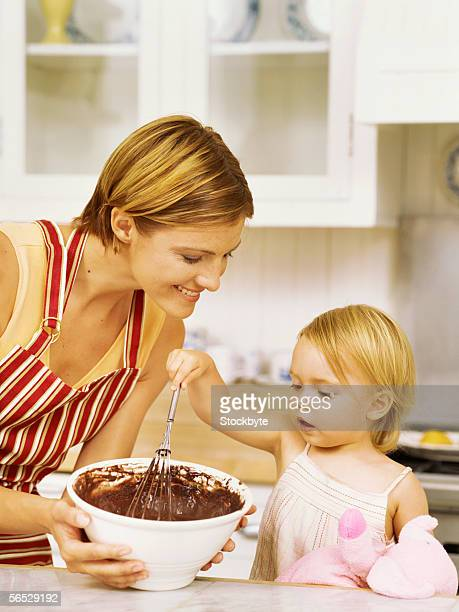 daughter using a whisk with her mother standing beside her