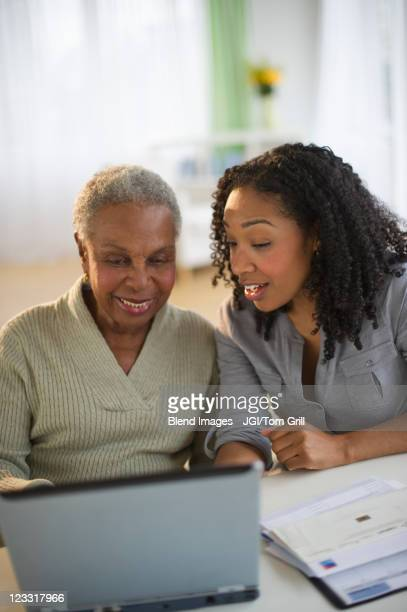 Daughter using laptop with mother