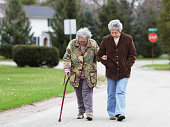 Daughter Walking with Mother Using Cane