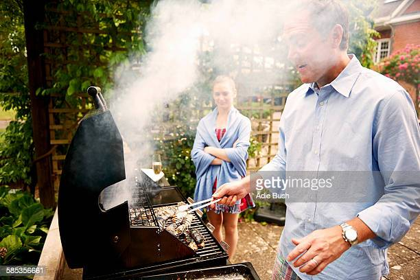 Daughter watching father cook sea food on barbecue