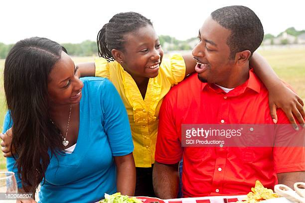 Daughter With Arms Around Her Parents at the Picnic Table