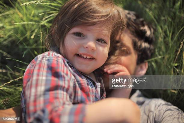 Daughter with father smiling on grass