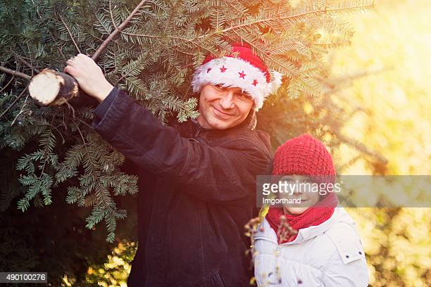 Daughter with father that carries tree for christmas.