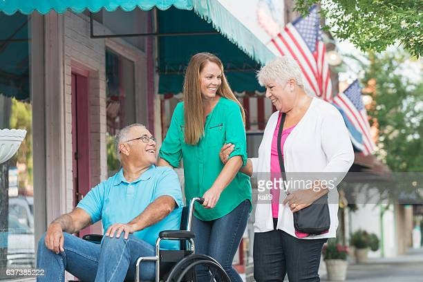 Daughter with senior parents, dad in wheelchair