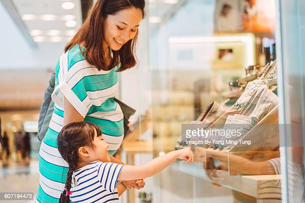 Daughter & young mom doing window shopping