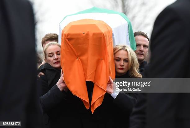 Daughters Fionnuala McGuinness and Grainne McGuinness carry the coffin of their father the late Martin McGuinness to the funeral service at St...
